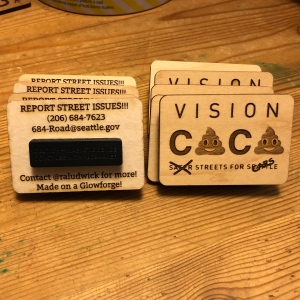 Image of a set of Glowforge printed wooden buttons with a Vision Caca logo on one side and instructions for reporting street issues on gthe other side.