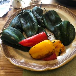 A bowl of roasted and skinned poblanos and small sweet red and yellow peppers