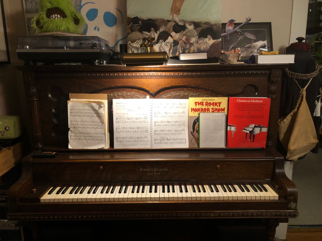 A dark brown upright piano from Franklin Piano Co sits with the keys showing. On the leaned out music stand is a piano method open to a version of Amazing Grace. Classics to Moderns and the Rocky Horror Show song book are closed to the right with a notebook. On top of the piano is a record player, a lamp, some other books and various pieces of art which are too long to describe here (email me!)